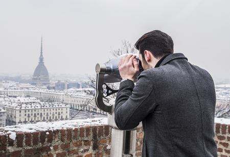 Back view of unrecognizable stylish man watching sights through binoculars in winter in Turin, Italy.