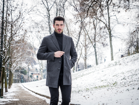 Handsome young stylish man looking at camera while walking in park in snowy day. Stock fotó