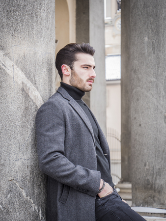 Handsome bearded young man outdoor in winter fashion, wearing black turtleneck sweater and woolen blazer jacket in city setting
