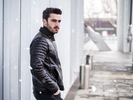 Handsome bearded young man outdoor in winter fashion, wearing black leather jacket in modern city setting Stock fotó