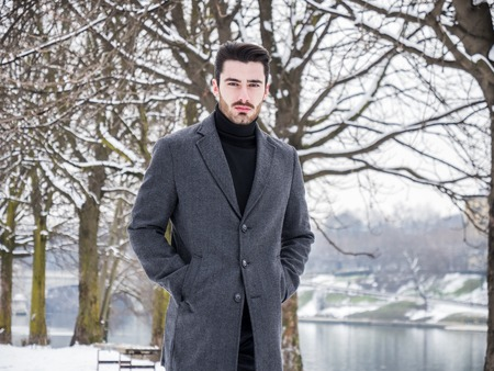 Handsome young stylish man looking at camera while walking in city park in snowy day.