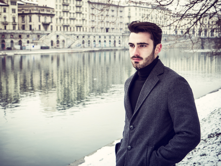 Handsome young man standing outside in winter, in snowy Turim, in Italy, on river docks Stock fotó