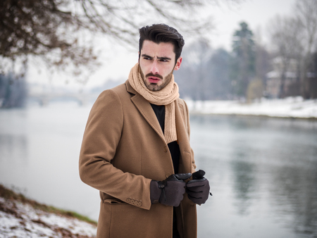 Handsome young man standing outside in winter, in snowy Turin, in Italy, on river docks Stock fotó