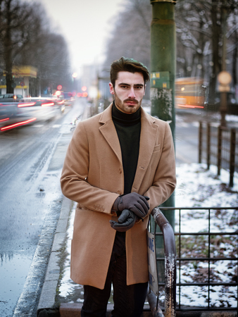 Handsome young man standing outside in winter, in snowy city. Cold urban setting