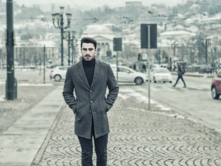 Handsome young man standing outside in winter, in snowy Turin, in Italy, in urban setting Stock fotó