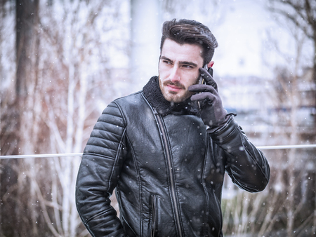 Handsome trendy man wearing black leather jacket standing and talking on cell phone, outdoor in city setting in winter day shot