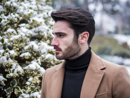 Handsome young man standing outside in winter, in snowy city park. Cold urban setting