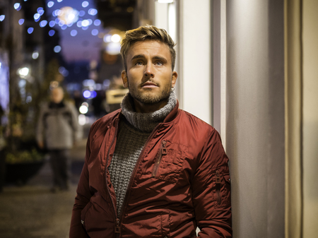 Handsome young man outdoor in winter fashion, wearing black coat and woolen scarf in city park Stock fotó