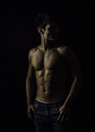 Handsome, fit muscular young man shirtless, wearing only jeans standing on black background, looking away to a side