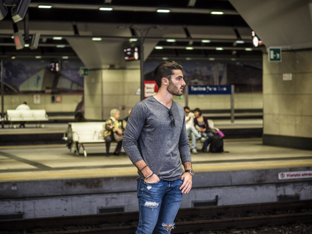 Handsome young male traveler in train station, looking to a side Stock fotó