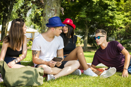 Young handsome men and attractive women sitting on grass lawn talking and enjoying themselves