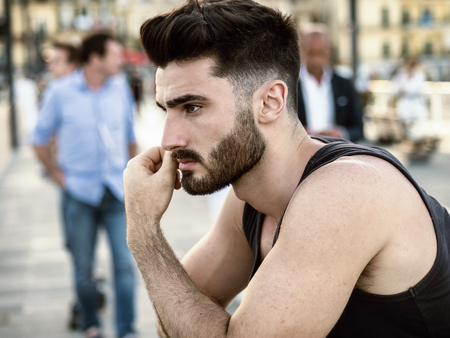 Attractive sad, worried young man thinking, at sunset on seaside boardwalk or seafront, wearing black tank-top, looking at the sea or ocean