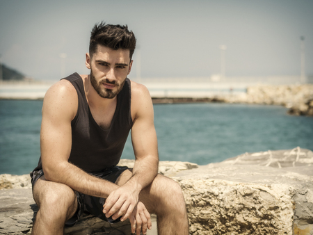 Attractive fit athletic young man soaking in the sun on seaside boardwalk or seafront, sitting on rock, wearing black tank-top