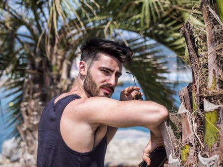 Attractive fit athletic young man at sunset on seaside boardwalk or seafront, leaning against palm tree, wearing black tank-top, looking at camera