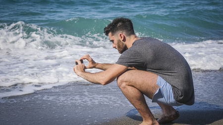Full body shot of a handsome young man using cell phone to take photo, crouching on a beach, wearing boxer shorts and dark t-shirt Archivio Fotografico - 104575116