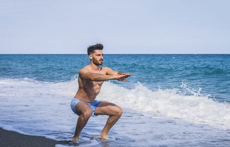 Athletic attractive young man exercising and working out with body weight by the sea, doing squats on sandy beach Stock Photo