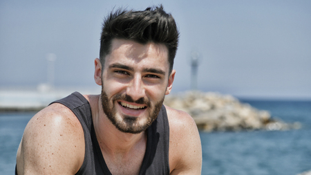 Attractive fit athletic young man soaking in the sun on seaside boardwalk or seafront, sitting on rock, wearing black tank-top, looking at camera with a smile