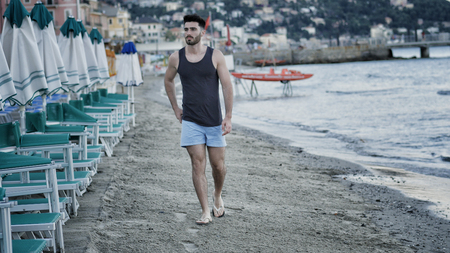 Attractive fit athletic young man walking along the beach among lounge chairs and sun umbrellas, wearing black tank-top