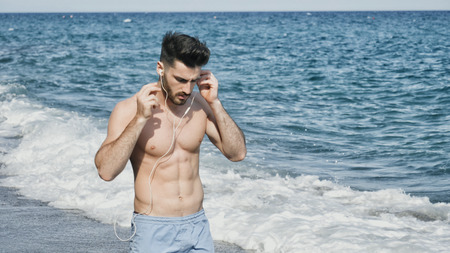 Solitary muscular young man standing on the beach while listening to music through earphones