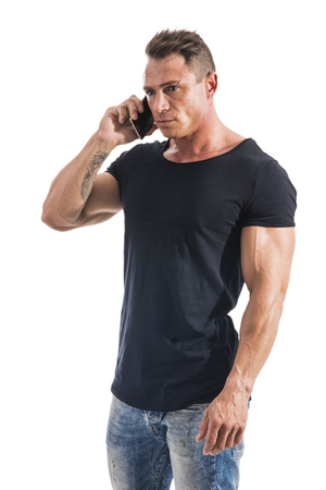 Handsome shirtless muscular bodybuilder man making a call with cell phone while standing isolated on white background
