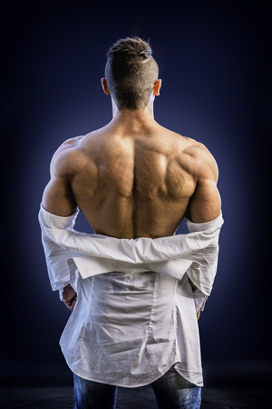 Rearview of back of male bodybuilder opening his shirt revealing muscular torso, on black background