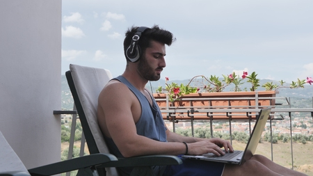 Waist Up Profile of Attractive Man with Dark Hair, Sitting with Laptop Computer Listening to Music with Big Headphones