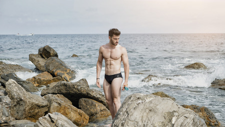 Attractive fit athletic young man soaking in the sun at rocky beach in front of the sea, shirtless