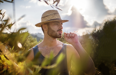 Attractive, fit young farmer man relaxing walking in a grass field, wearing straw hat