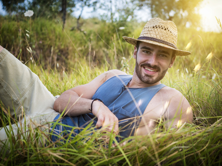 Attractive, fit young man relaxing laying down in a grass field, wearing straw hat, looking at camera, smiling