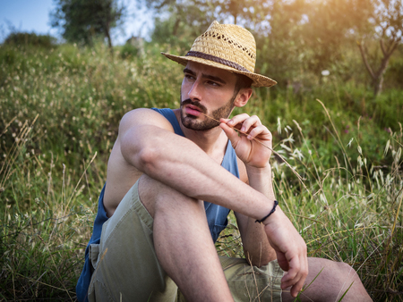 Attractive, fit young farmer man relaxing sitting in a grass field, wearing straw hat Stock Photo