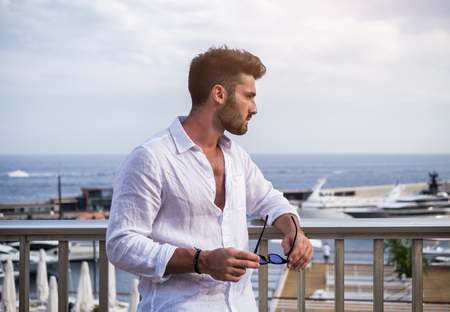 Attractive fit athletic young man soaking in the sun on seaside boardwalk or seafront, wearing white shirt in Montecarlo, Monaco on the French Riviera