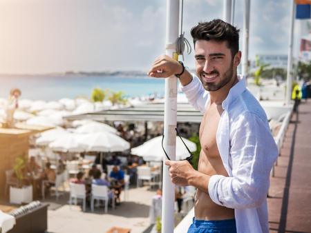 Attractive fit athletic young man soaking in the sun on seaside boardwalk or seafront, wearing white shirt in Nice, France on the French Riviera