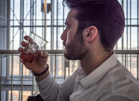 Portrait of stylish young man wearing business suit, drinking cocktail next to window overlooking modern European city