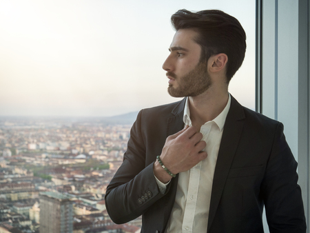 Portrait of stylish young man wearing business suit, standing next to window overlooking modern European city