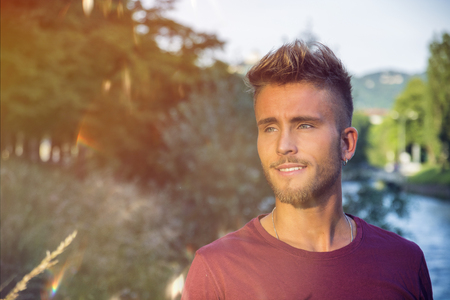 Blondish, blue eyed young man by river at sunset, thinking, looking at camera