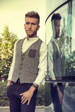 Blond Young Man Next to Modern Building in City, Wearing White Shirt and Elegant Vest, Standing and Leaning against Glass Wall