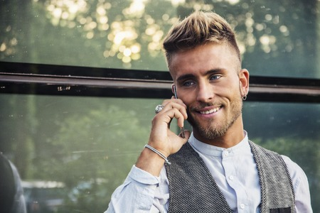 Stylish trendy young man talking on cell phone, outdoor next to office window, looking away, confident expression and a smile
