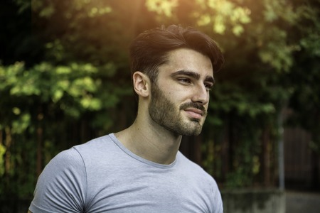 Handsome young man outdoor looking away to a side