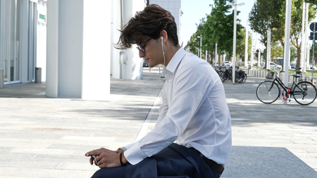 Stylish Young Handsome Man with Earphones Watching Video or Film on Smartphone, Sitting in City Center Street
