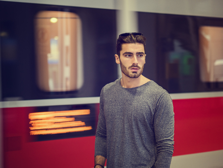 Handsome young male traveler in train station with moving train behind him, looking to a side
