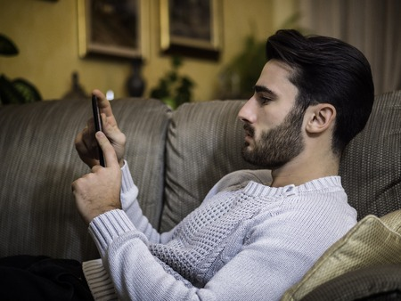 Handsome young man at home, reading with ebook reader lying on a couch