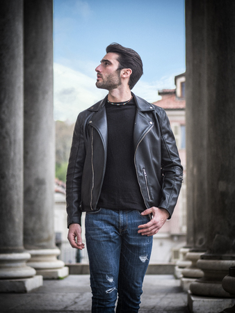 One handsome young man in urban setting in modern city, standing, wearing black leather jacket and jeans, looking away