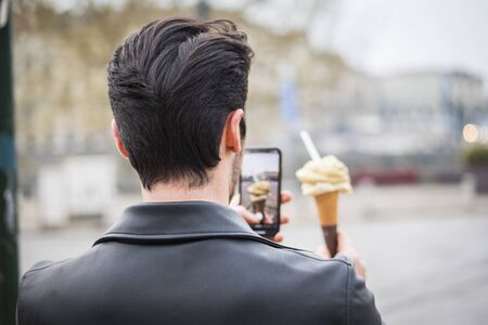 Attractive young man standing, wearing black leather jacket while taking mobile photo of a tasty ice cream outdoors in city