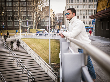 One attractive man in urban setting in modern city, leaning on metal handrail, wearing wool sweater and sunglasses, looking away