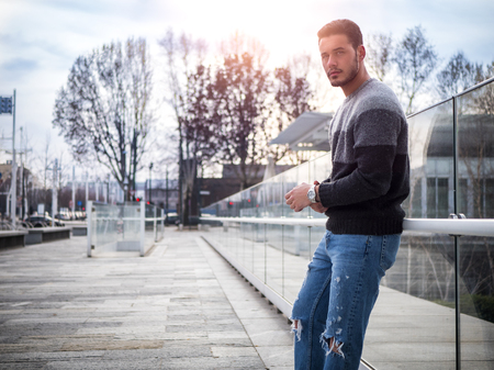 One attractive man in urban environment in city, leaning on glass wall, wearing wool sweater, looking at camera