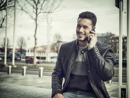 Handsome trendy young man wearing black leather jacket, sitting and talking on cell phone while smiling, outdoor in city setting in day shot
