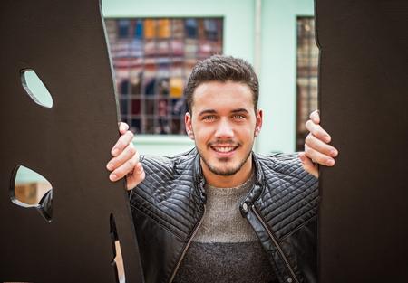 Happy, smiling young man in black between metal doors looking at camera Imagens