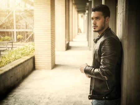 Attractive young man in narrow columns corridor outdoors, profile view