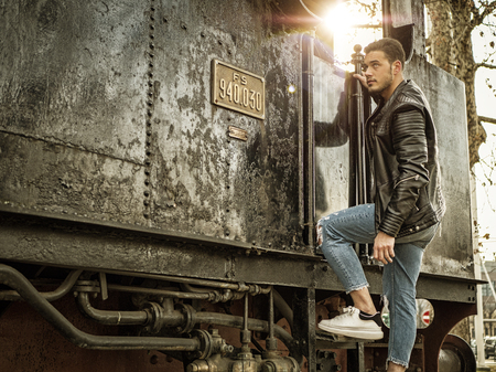 Handsome young man in black leather jacket near old train, leaning against it, looking away Imagens