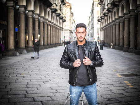 One handsome young man in urban setting in old classic European city, standing, wearing black leather jacket and jeans, looking at camera in Turin, Italy Imagens